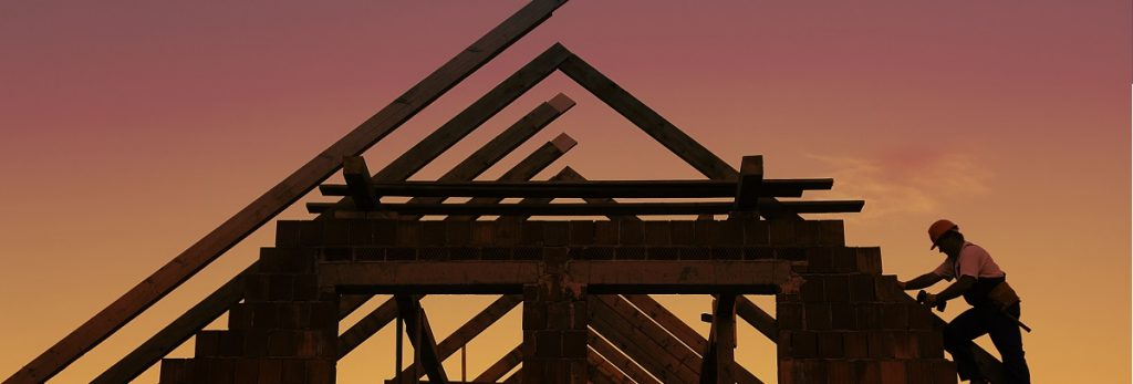 robotnik mocujący więźbę dachową